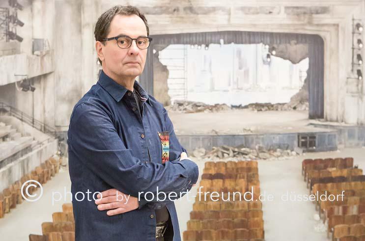 Fotograf Robert Freund in Düsseldorf fotografiert Fotografen Verleger Gerhard Steidl als Portrait Fotografie vor dem Chanel Mode Laufsteg von Karl Lagerfeld.